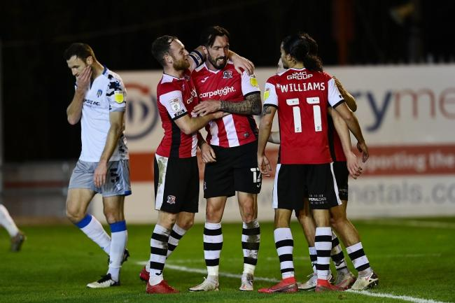Contrasting emotions - Exeter City's Ryan Bowman  celebrates with his team-mates after scoring while U's defender Tommy Smith is left to contemplate a bad night for the visitors Picture: Tom Sandberg/PPAUK