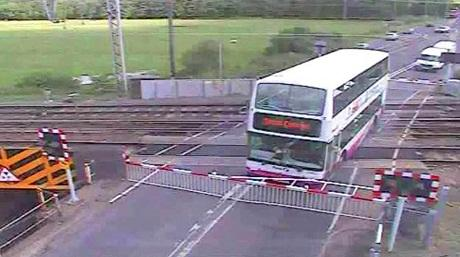 Dozy bus driver stuck on train tracks captured on CCTV