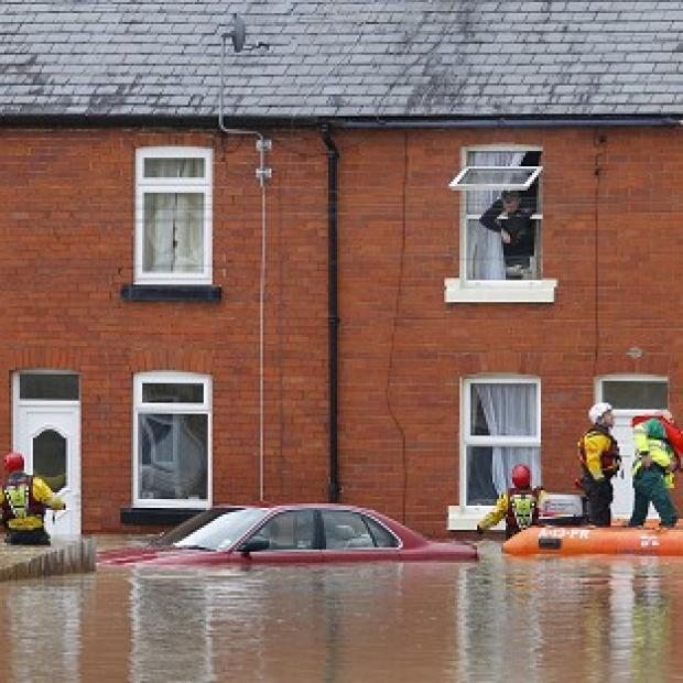 Maldon and Burnham Standard: A man looks out of a window as a crew from the RNLI and paramedics pass a submerged car in St Asaph, Denbighshire