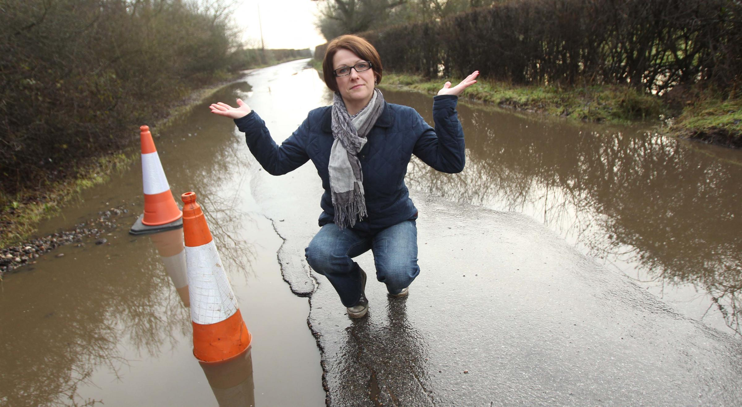 Corinne Jacques at the site of the large pothole