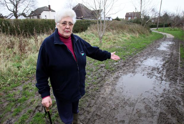Nancy Crisp, of Fernlea Road, Burnham, shows the state of the path leading to Riverside Park