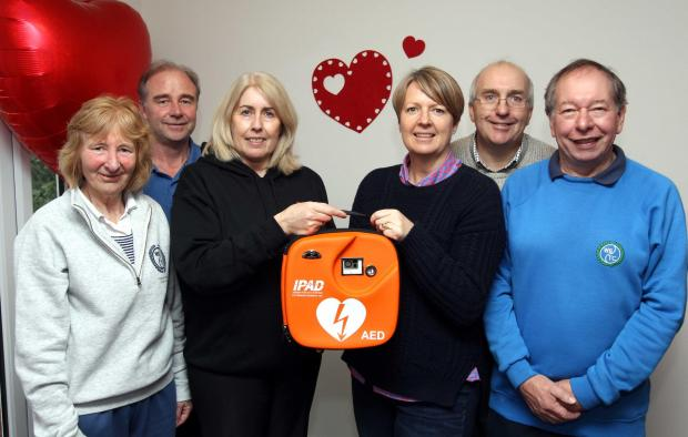 Lynn O'Brien (centre left) presenting defibrillator to Jenny Cooper (centre right), l-r Jan Rochester, Graham Lewis-Taylor, Richard Hurford and Bill Stephens