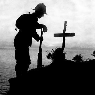 A British soldier pays his respects at the grave of