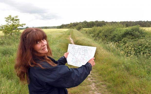 Annie Gordon from the Essex Wildlife Trust at Heybridge Wood, with a plan of the garden suburb that could surround it