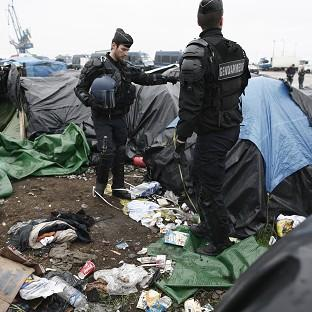 Maldon and Burnham Standard: Police officers take positions in a makeshift camp housing hundreds of illegal migrants from Syria, Afghanistan and Africa, after French authorities started to clear out camps in Calais