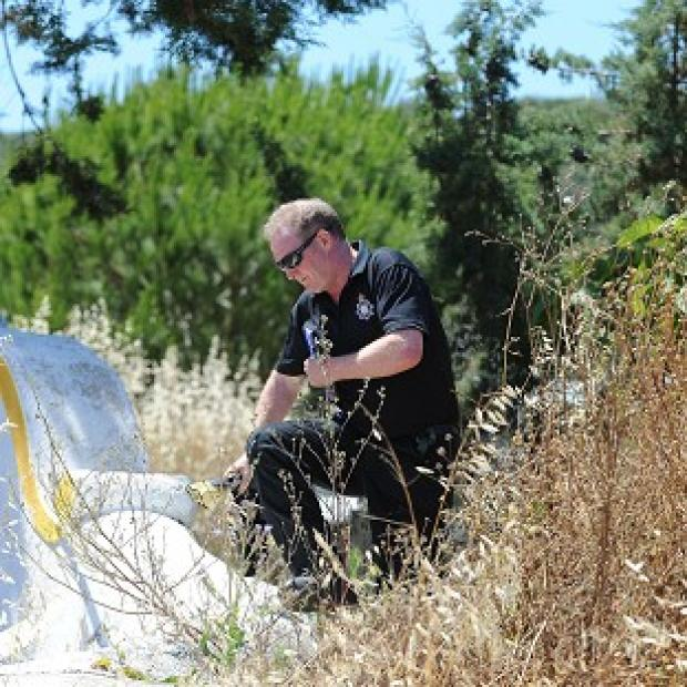 Maldon and Burnham Standard: A British police officer scrambles over a wall as British and Portuguese officers investigate the disappearance of Madeleine McCann from Praia da Luz