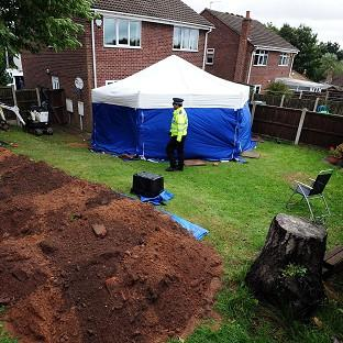 Police in the garden of a house in Mansfield, where the remains of William and Patricia Wycherley were discovered