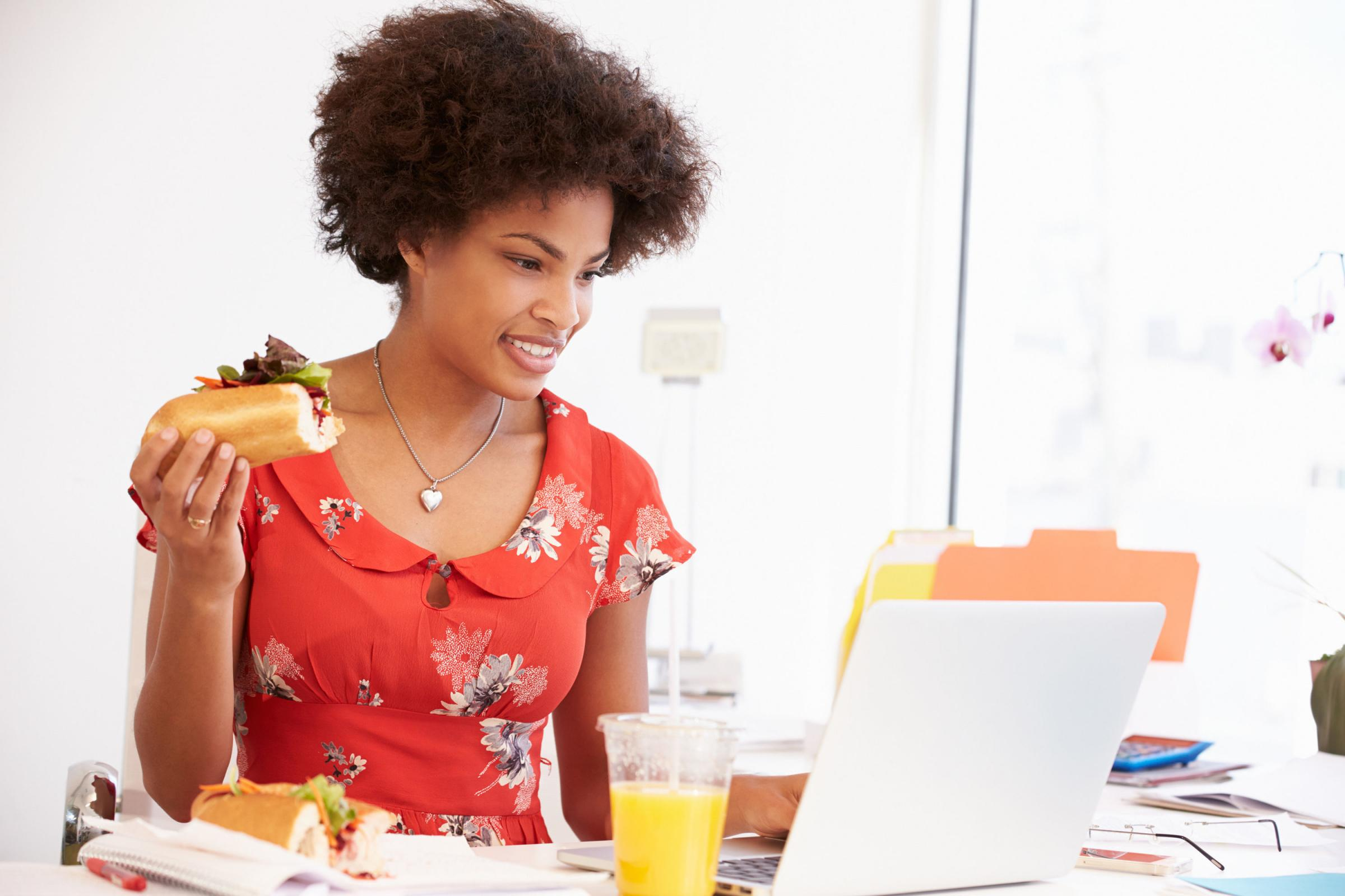 Woman Working In Design Studio Having Lunch At Desk